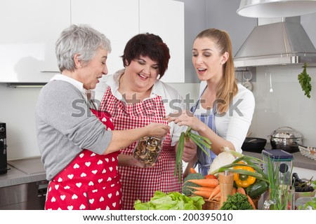 Three girlfriends cooking together at home. - stock photo