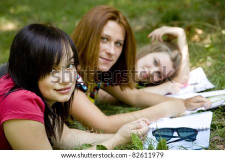 Three girlfriends doing homework at the park. - stock photo