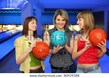 Three girlfriends hold balls for bowling and look on each other, focus on  girl in center
