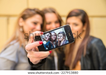 Three girlfriends taking a selfie with smart phone - Happy women having fun outdoors - stock photo