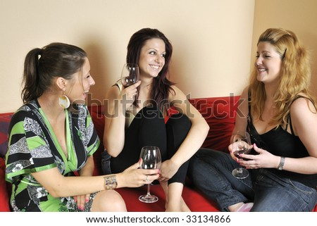 three girls are drinking a glass of wine
