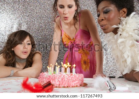 Three girls blowing the candles of a birthday cake at a party, against a silver glitter background.