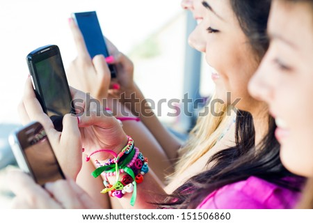 three girls chatting with their smartphones at the park - stock photo