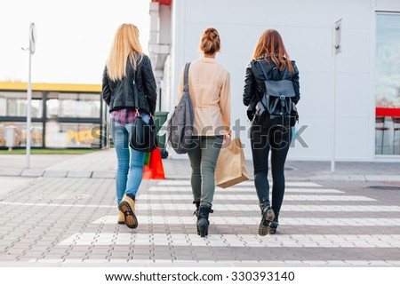 Three girls crossing the street after shopping - stock photo