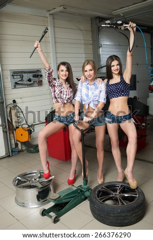 Three girls for tire. car repair - stock photo
