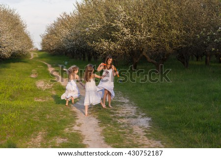 Three girls (friends, sisters) whirling, dancing, and burst bubbles