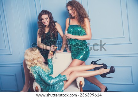 Three girls in evening dresses with champagne glasses - new year, celebration, friends, birthday concept
