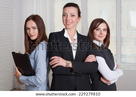 Three girls in formal clothes are of different heights with their arms crossed