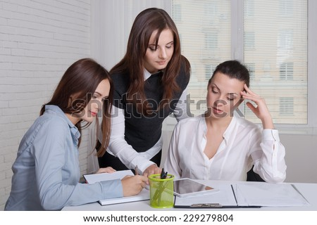 Three girls in formal clothes holds a meeting by reading the information on the tablet