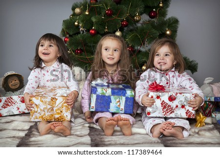 Three girls in pajamas sitting under the Christmas tree with gifts in their hands - stock photo