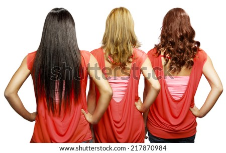 Three girls in red with different hair colors from behind. - stock photo