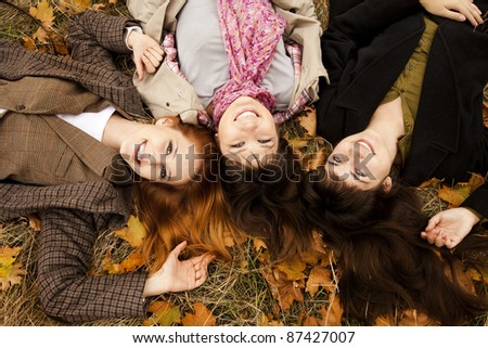 Three girls in the autumn park. Outdoor shot. - stock photo