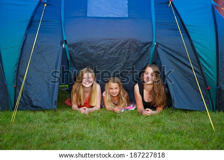 three girls looking out of their camping tent - stock photo