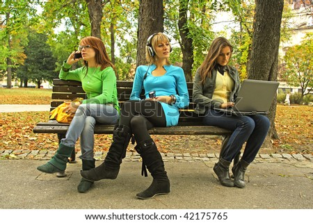 "Three girls on a bench. In ""three different world"" with no friendship."