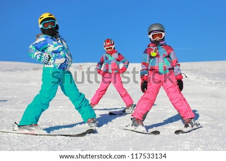 Three girls on the snow with ski equipment - stock photo
