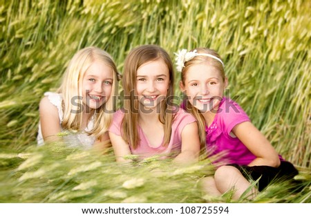 Three girls or friends sitting in a wheatfield - stock photo