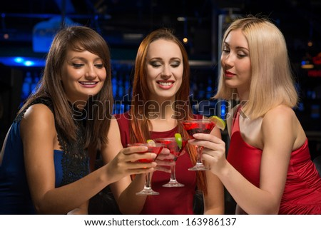 three girls raised their glasses in a nightclub, have fun with friends