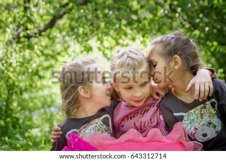 Three girls sharing secrets on ear outdoor