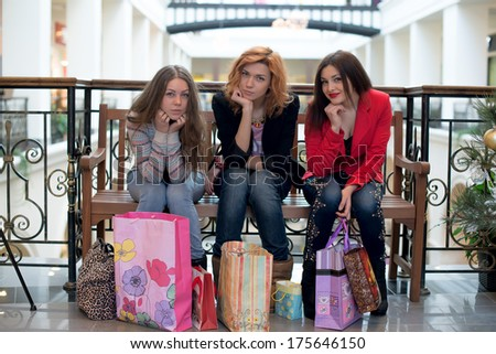 Three girls sitting on a bench in the mall and discuss their purchases
