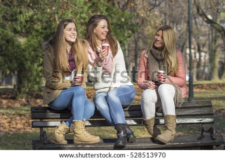 Three girls sitting on the bench in park and drink coffee