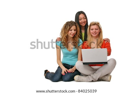 Three girls sitting on the floor with a laptop. isolated on white background. Lots of copyspace - stock photo