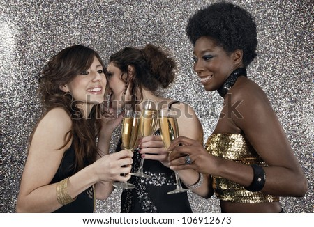 Three girls toasting with champagne at a party with a silver glitter background.