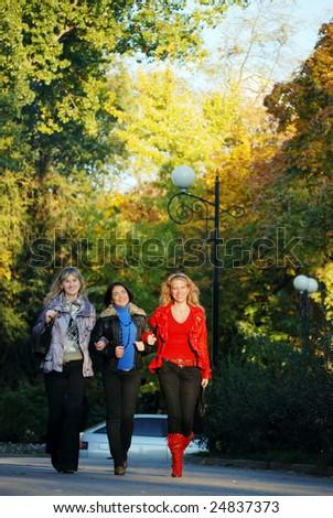 Three girls walk on park and smile - stock photo