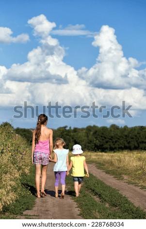 three girls walking at the outdoors  - stock photo