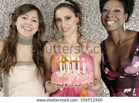 Three girls with a birthday cake and candles against a silver glitter background, smiling. - stock photo