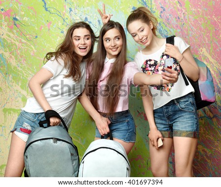 three girls with backpacks taking pictures of himself on the phone - stock photo
