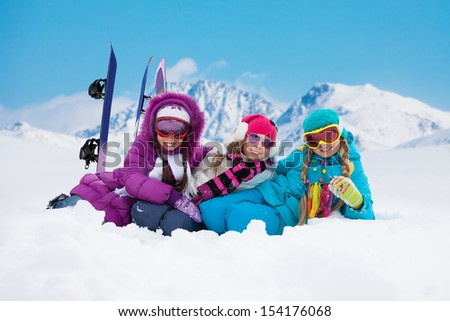 Three girls with snowboards laying on the snow in mountains