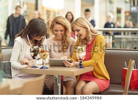 Three gladsome ladies in the coffee shop - stock photo