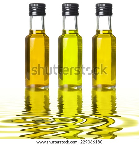 Three glass bottles of different extra olive oil on liquid reflections - stock photo