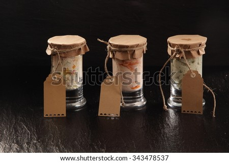 Three glass jars of homemade savory dips sealed with paper and string, each with a blank brown, gift tag, on a textured slate counter