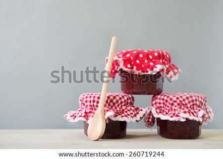 Three glass pots of home made jam with wooden spoon - stock photo