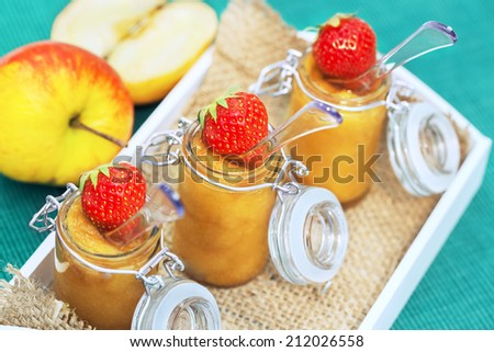 Three glasses of apple compote with strawberry decoration on a tray - stock photo