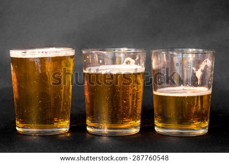 Three glasses of beer, one full, one half full and one empty  - stock photo