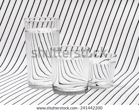 Three glasses of clear water on striped cloth. Refraction, light bending science effect. - stock photo