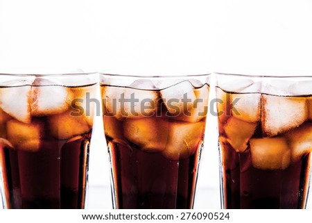 three glasses of cola and ice on a white background. soft drinks - stock photo