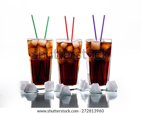 three glasses of cola with ice and straws on a white background. soft drinks - stock photo