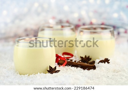Three glasses of fresh eggnog with cinnamon sticks and star of anise ready for the Christmas season with copy space. Extreme shallow depth of field.