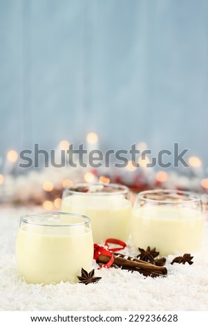 Three glasses of fresh eggnog with cinnamon sticks and star of anise ready for the Christmas season with copy space. Extreme shallow depth of field. - stock photo
