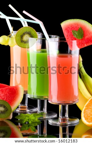 Three glasses of organic juice made from fresh fruits and surrounded by fresh ones. Series about organic and healthy drinks. - stock photo