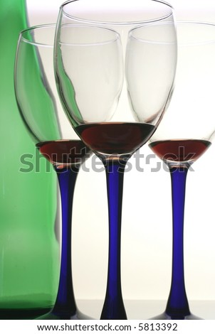 Three glasses of  red wine with blue stems and a green bottle.