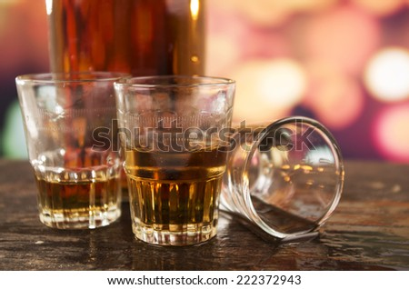 Three Glasses Of Rum Whiskey Alcohol On Wooden Table Over Defocused Lights  Background