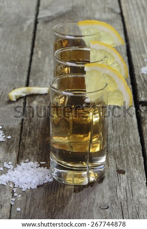 Three glasses of tequila with lemon and salt on a wooden table - stock photo