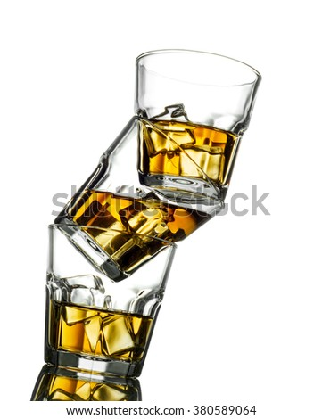 Three glasses of whiskey on the rocks, one on top of the other.