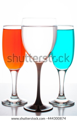 three glasses of wine with colored liquids on a white background