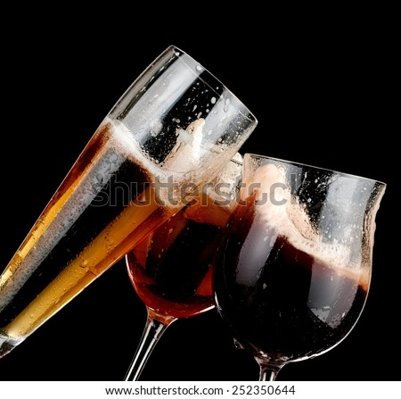 Three glasses with beer on black background