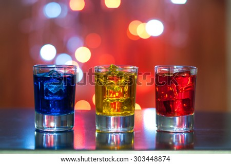Three glasses with berry liqueur on the bar counter at a nightclub, magic light bokeh.
